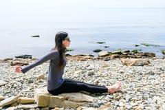 La yoga practicante de la muchacha en las rocas se coloca en una piedra Imágenes de archivo libres de regalías