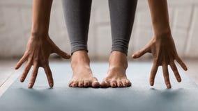 La yoga practicante de la mujer, actitud del uttanasana, cabeza a las rodillas se cierra para arriba imagen de archivo libre de regalías