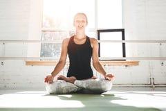 La yoga practicante de la mujer apta de Happines presenta en gimnasio en mowrning Hembra en actitud de la yoga en la estera de la foto de archivo libre de regalías