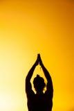 La yoga practicante del hombre en la luz de la puesta del sol Fotos de archivo