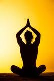 La yoga practicante del hombre en la luz de la puesta del sol Fotografía de archivo