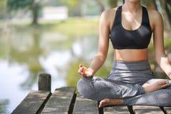 La yoga practicante en la naturaleza, felicidad femenina de la mujer joven, mujer asiática está practicando yoga en el lago de la imagen de archivo