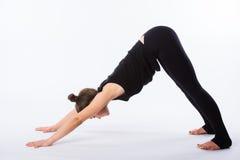 La yoga sana que estira a la mujer hace un perro boca abajo Éste es parte de una serie de diversas actitudes de la yoga al lado d Foto de archivo libre de regalías