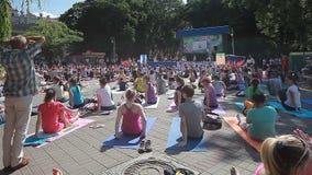La yoga video editorial de la gente clasifica durante el día de banquete de yoga en el parque en las esteras de una aptitud Bielo almacen de metraje de vídeo