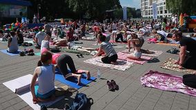 La yoga video editorial de la gente clasifica durante el día de banquete de yoga en el parque en las esteras de una aptitud Bielo almacen de video