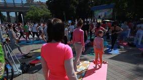 La yoga video editorial de la gente clasifica durante el día de banquete de yoga en el parque en las esteras de una aptitud Bielo metrajes