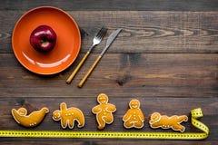 La yoga y la dieta sana para pierden el peso La placa con la manzana y las galletas en la forma de los asans de la yoga en fondo  Imagenes de archivo
