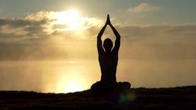 La yogui brillante se sienta en loto en un banco del lago y ruega en la puesta del sol en la cámara lenta
