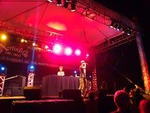 La yogui de la bujía métrica canta en el Mic con las pistas de giro de DJ Drez en etapa en Imagen de archivo