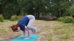 La yogui femenina hace el aire libre del bakasana, lento trasero sano de la balanza del asana simple de la yoga almacen de video