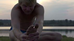 La yogui joven se sienta en un banco del lago y mantiene sus dedos del pie el slo-MES metrajes