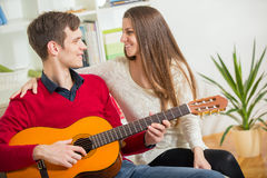 LA young and attractive couple sitting on a couch with a guitar. Royalty Free Stock Photo