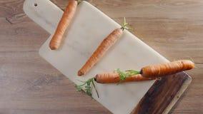 La zanahoria cae en la cámara lenta al tablero de la roca en la tabla, verduras que caen, comida en la cámara lenta estupenda,  metrajes