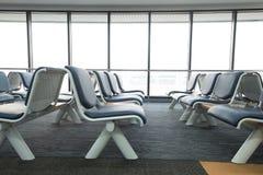 La zona de espera vacía del terminal de aeropuerto con las sillas gandulea con el asiento Imágenes de archivo libres de regalías
