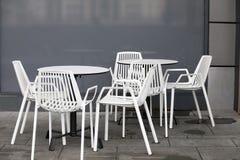 La zona del restaurante con las sillas plásticas blancas y las tablas blancas en el pasillo de la alameda Interior hermoso Fotografía de archivo