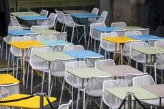 La zona del restaurante con las sillas plásticas coloridas y las tablas azules, amarillas, blancas en el pasillo de la alameda In Fotos de archivo libres de regalías