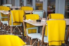 La zona del restaurante con las sillas plásticas coloridas y las tablas y la tela escocesa azules, amarillas, blancas en el pasil Imagen de archivo