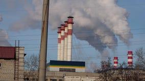 La zona industrial con un humo blanco grueso grande del tubo rojo y blanco se vierte del tubo de la fábrica en contraste con el s almacen de metraje de vídeo