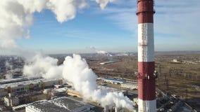 La zona industrial con un humo blanco grueso grande del tubo rojo y blanco se vierte del tubo de la fábrica en contraste con el s almacen de video