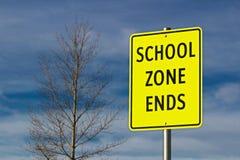 La zone d'école finit le signe sur le fond de ciel avec l'arbre Image stock