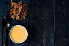 La zucca passa la minestra con bacon fritto su fondo nero fotografia stock libera da diritti