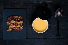 La zucca passa la minestra con bacon fritto su fondo nero fotografie stock libere da diritti