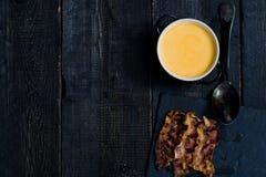 La zucca passa la minestra con bacon fritto su fondo nero immagini stock
