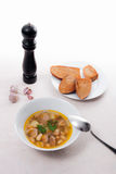La zuppa di fagioli in piatto bianco con il cucchiaio del metallo, vari tosta su briciolo Immagini Stock