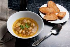 La zuppa di fagioli in piatto bianco con il cucchiaio del metallo, vari tosta su briciolo Fotografia Stock