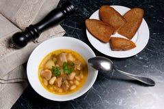 La zuppa di fagioli in piatto bianco con il cucchiaio del metallo, vari tosta su briciolo Fotografie Stock Libere da Diritti