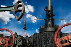 Laag Hoekweergeven van een Horsehead Pumpjack met Bewolkte Blauwe Hemel op Achtergrond stock foto