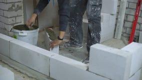 Laag schot van bouwer die mortier op gelucht concreet blok met spatel zetten stock video