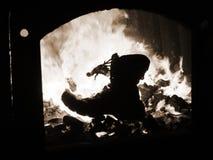 Laarzen militaire brandwonden in de oven van de brand van oorlog Stock Foto's