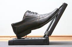 Laarzen op laptop Stock Afbeeldingen