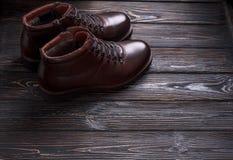 Laarzen van het mensen` s de bruine leer op donkere houten achtergrond Stock Foto