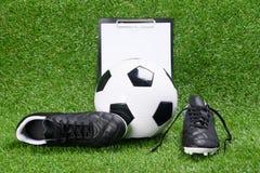 Laarzen, voetbalbal en tablet voor het schrijven, tegen de achtergrond van gras stock fotografie