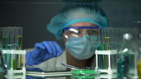 Lab assistant adding green powder to tube and typing result on tab, technology