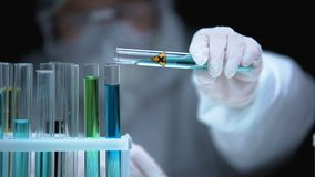 Lab assistant adding liquid from test tube with cross symbol, illegal research. Stock footage stock video footage