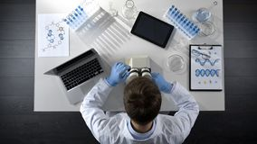 Lab assistant adjusting microscope objective, researching material, top view stock photo