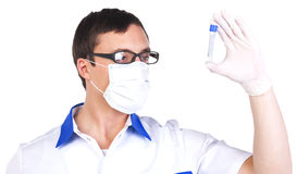 Lab assistant checking a  test tube. Laboratory assistant in glasses and breather looking at a test tube Stock Photography