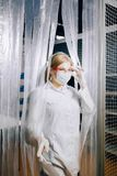 The lab assistant girl comes out of the lab. Closed lab. stock image