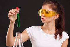 A lab assistant holds a closed test tube on a black background. A lab assistant in glasses and a white T-shirt is holding a closed test-tube with a green liquid stock photos