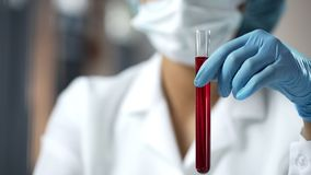 Lab assistant holding test tube with red liquid, blood analysis researching stock photography