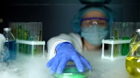 Lab assistant taking green powder from fridge, dermatology cryotherapy material. Stock photo royalty free stock image