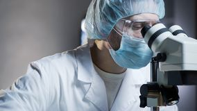 Lab assistant viewing samples in microscope, conducting chemical research stock photo