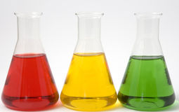 Lab beakers with liquid. Three laboratory glass beakers in a row filled with red, yellow and green liquid Stock Photo
