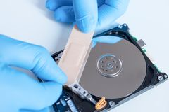 Lab engineer working on broken hard disk. Lab engineer repairing and fixing broken hard disk for data recovery Royalty Free Stock Photography