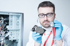 Lab engineer working on broken hard disk. Lab engineer repairing and fixing broken hard disk for data recovery Stock Photos