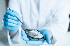 Lab engineer working on broken hard disk. Lab engineer repairing and fixing broken hard disk for data recovery Stock Image