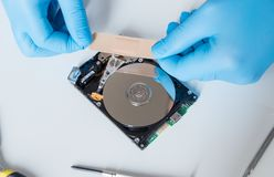Lab engineer working on broken hard disk. Lab engineer repairing and fixing broken hard disk for data recovery Stock Photo